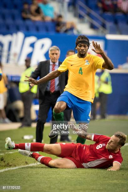 Scott Arfield of Canada slides to stop the advance by Rhudy Evens of French Guiana during the CONCACAF Gold Cup Match between Canada and French...