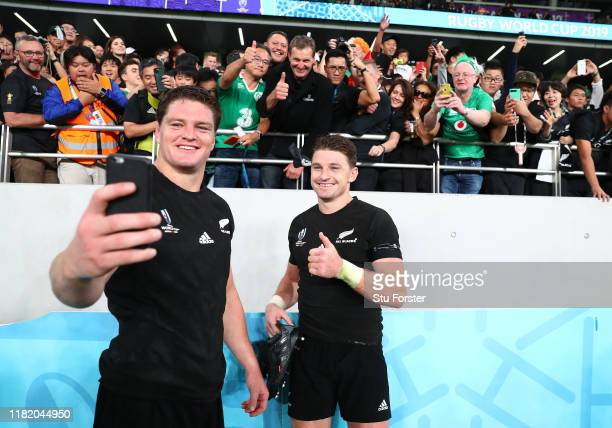 Scott Barrett and Beauden Barrett of New Zealand take a selfie with fans following the Rugby World Cup 2019 Quarter Final match between New Zealand...