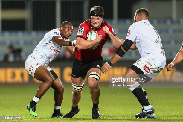Scott Barrett of the Crusaders attempts to evade Makazole Mapimpi and Thomas du Toit of the Sharks during the round 12 Super Rugby match between the...