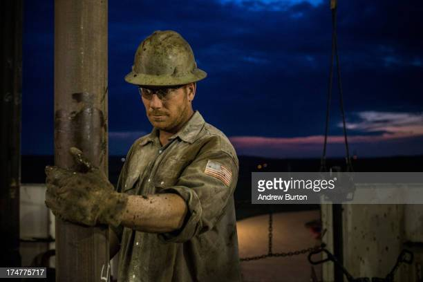 Scott Berreth a derrick hand for Raven Drilling works on an oil rig drilling into the Bakken shale formation on July 28 2013 outside Watford City...