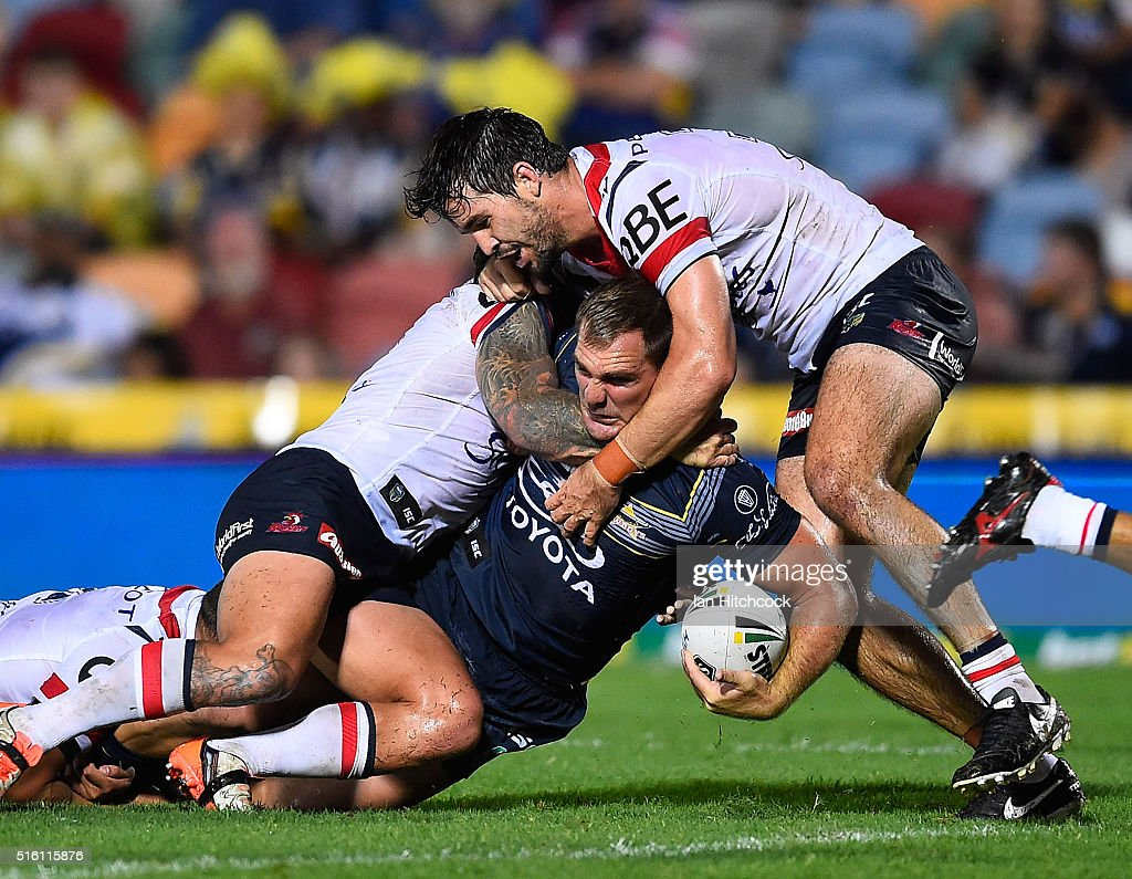 Scott Bolton of the Cowboys is tackled by Aidan Guerra and Jake Friend of the Roosters during the round three NRL match between the North Queensland Cowboys and the Sydney Roosters at 1300SMILES Stadium on March 17, 2016 in Townsville, Australia.