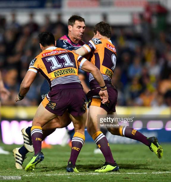 Scott Bolton of the Cowboys is tackled by Alex Glenn and Andrew McCullough of the Broncos during the round 22 NRL match between the North Queensland...