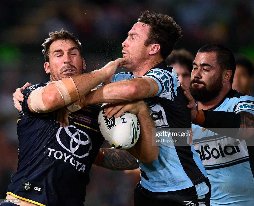 Scott Bolton of the Cowboys is tackled by James Maloney and Andrew Fifita of the Sharks during the round 24 NRL match between the North Queensland Cowboys and the Cronulla Sharks at 1300SMILES Stadium on August 19, 2017 in Townsville, Australia.