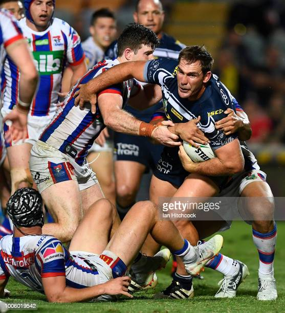 Scott Bolton of the Cowboys is wrapped up by the Knights defence during the round 20 NRL match between the North Queensland Cowboys and the Newcastle...