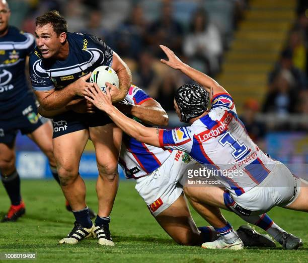 Scott Bolton of the Cowboys looks to get the ball away during the round 20 NRL match between the North Queensland Cowboys and the Newcastle Knights...