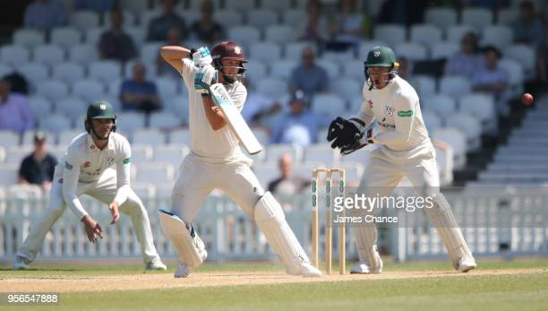 Scott Borthwick of Surrey bats as Joe Clarke of Worcestershire looks on during Day Four of the Specsavers County Championship Division One match...