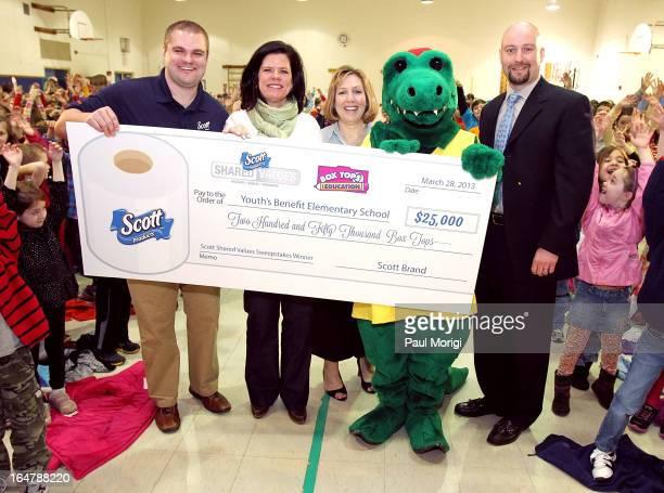 Scott Brand Manager Ben Johnson presents a $25000 check to Box Tops Coordinator Jenn Stump PTA President Laura Runyeon Mascot Al E Gator and...