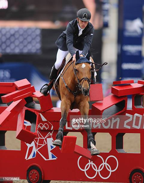 Scott Brash of Great Britain on Ursula XII piles through the London 2012 bus during the Longines Global Champions Tour of London on Day Four at...