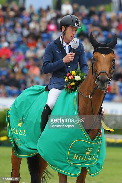 Scott Brash of GreatBritain rides on Hello Sanctosh and and speaks to the audience during the podium after winning the Rolex Grand Prix jumping...