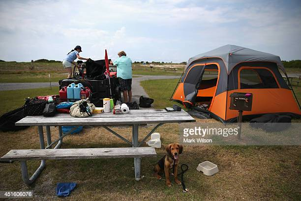 Scott Brooks and Hannah Thomas of Boston MA break down their campsite while their dog sits nearby on July 2 2014 in Oregon Inlet North Carolina Cape...
