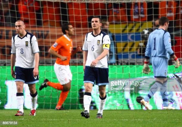 Scott Brown Barry Ferguson and Allan McGregor of Scotland look dejected after the first goal of Klaas Jan Huntelaar of the Netherlands during the...