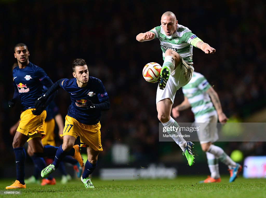 Scott Brown of Celtic keeps the ball moving past Massimo Bruno of FC Salzburg during the UEFA Europa League group D match between Celtic FC and FC Salzburg at Celtic Park on November 27, 2014 in Glasgow Scotland.