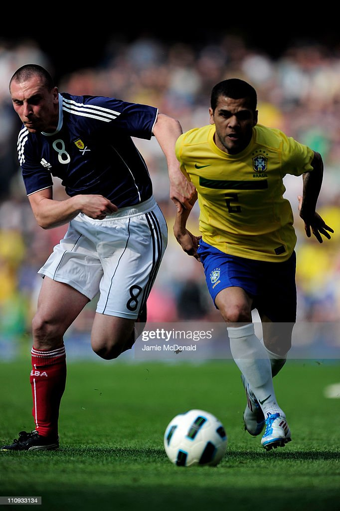 Scott Brown of Scotland and Daniel Alves of Brazil chase the ball during the International friendly match between Brazil and Scotland at Emirates Stadium on March 27, 2011 in London, England.