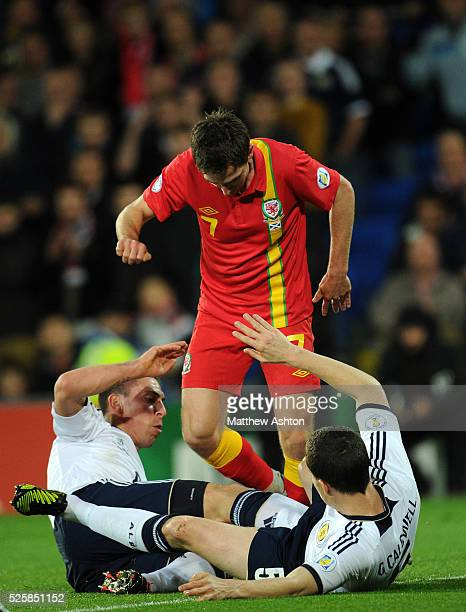 Scott Brown of Scotland and Gary Caldwell of Scotland tackle Joe Allen of Wales