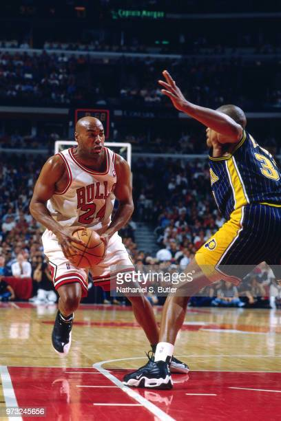 Scott Burrell of the Chicago Bulls drives as Antonio Davis of the Indiana Pacers defends during a game played on May 27 1998 at the United Center in...