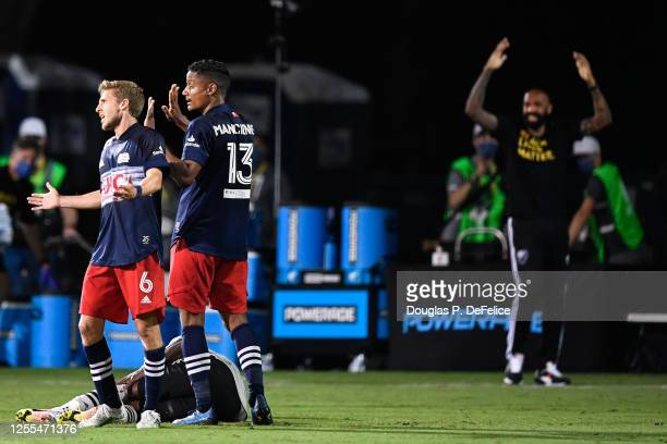 Scott Caldwell Michael Mancienne of New England Revolution and Thierry Henry head coach of Montreal Impact react to a call by the referee during the...