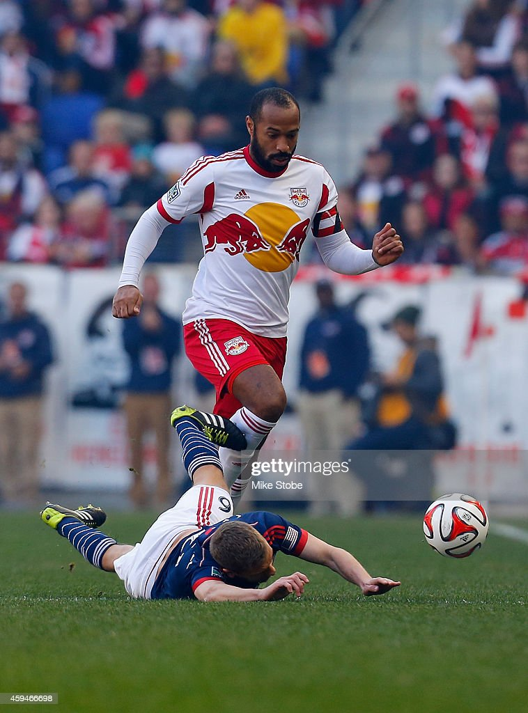 Scott Caldwell #6 of New England Revolution is tripped up by Thierry Henry #14 of New York Red Bulls during the Eastern Conference Final - Leg 1 at Red Bull Arena on November 23, 2014 in Harrison, New Jersey. Revolution defeated the Red Bulls 2-1.