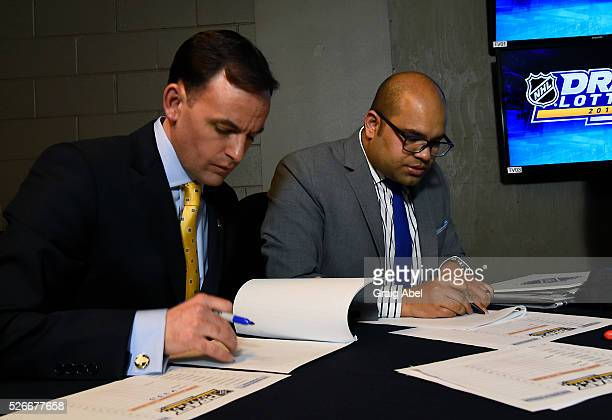 Scott Clarke and Lionel Coutinho of Ernst and Young cross check their lists during The National Hockey League Draft Lottery at the CBC Studios in...
