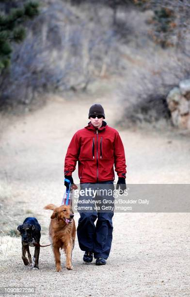 Scott Clemens , walks his golden retriever, Logan, and catahoula leopard dog, Sarabi, down the trail at Sanitas Trailhead in Boulder, Colorado...