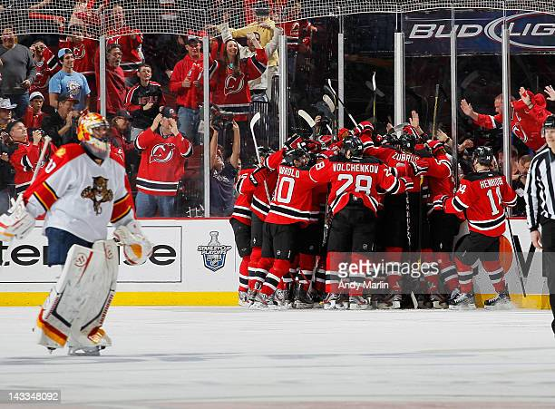 Scott Clemmensen of the Florida Panthers skates away dejected as Travis Zajac of the New Jersey Devils is congratulated by his teammates after...