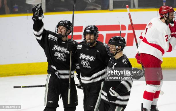 Scott Conway of the Providence College Friars celebrates his second period goal against the Cornell Big Red with his teammates Jacob Bryson and Josh...