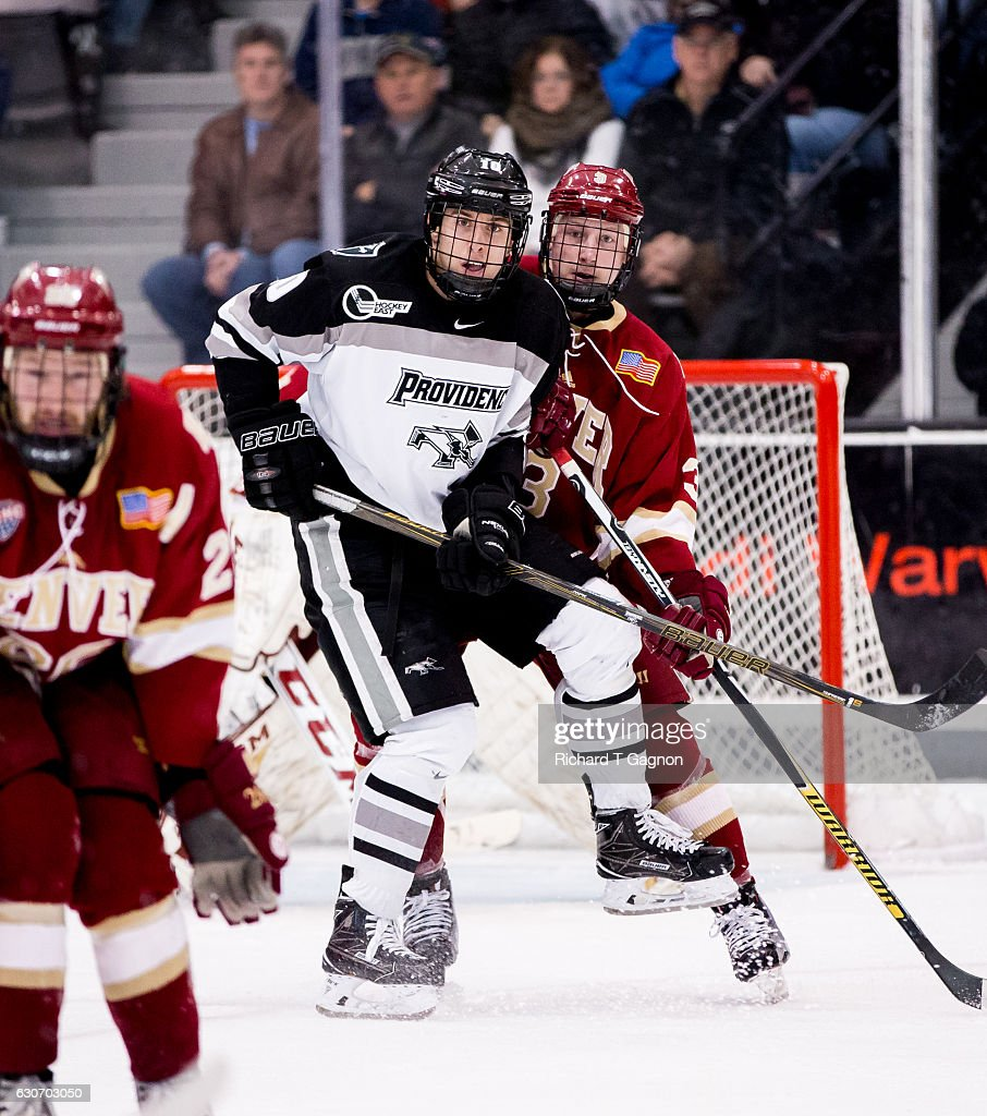 Scott Conway #10 of the Providence College Friars checks Tyson McLellan #9 of the Denver Pioneers during NCAA hockey at the Schneider Arena on December 30, 2016 in Providence, Rhode Island. The game ended in a 2-2 tie.