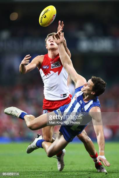 Scott D Thompson of the Kangaroos is challenged by Will Hayward of the Swans during the round seven AFL match between the Sydney Swans and the North...