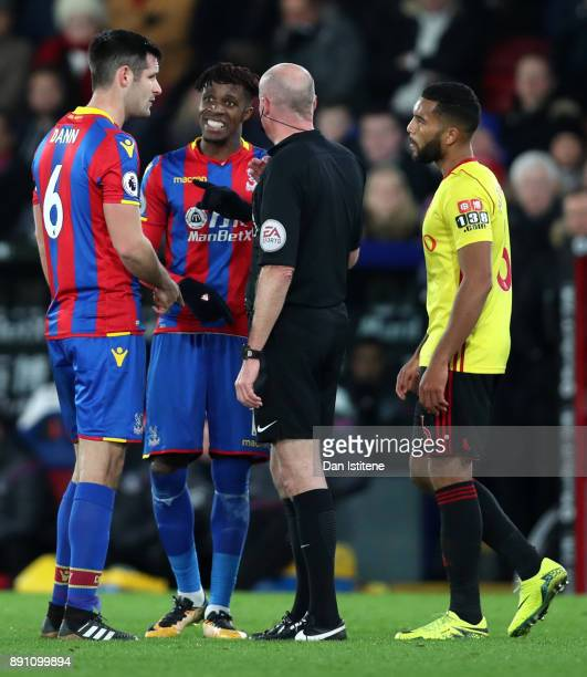 Scott Dann of Crystal Palace and Wilfried Zaha of Crystal Palace confront referee Lee Mason during the Premier League match between Crystal Palace...