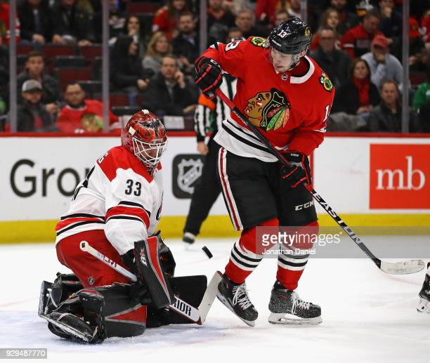 Scott Darling of the Carolina Hurricanes makes a stop behind Tomas Jurco of the Chicago Blackhawks at the United Center on March 8 2018 in Chicago...