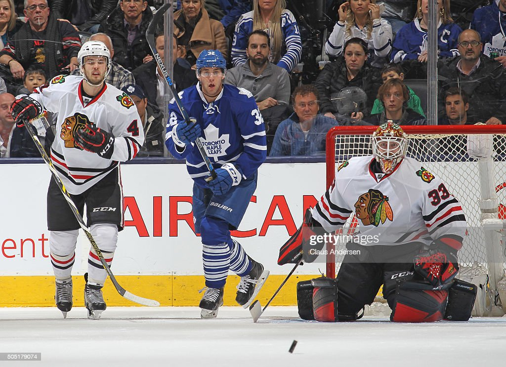 Scott Darling #33 of the Chicago Black Hawks watches for a shot next to Josh Leivo #32 of the Toronto Maple Leafs during an NHL game at the Air Canada Centre on January 15, 2016 in Toronto, Ontario, Canada. The Black Hawks defeated the Maple Leafs 4-1.