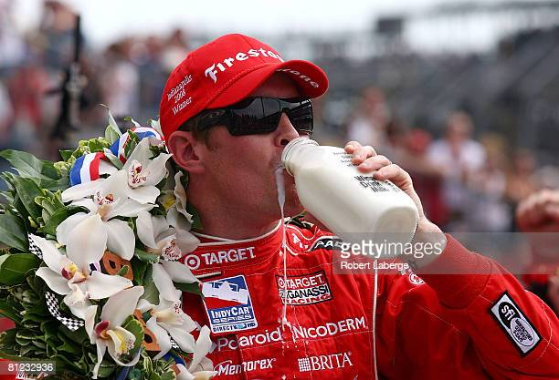 Scott Dixon driver of the Target Chip Ganassi Racing Dallara Honda drinks the ceremonial winner's milk over in victory lane in celebration of winning...