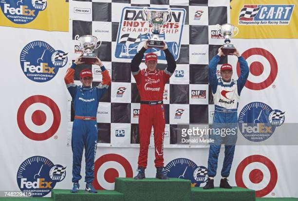 Scott Dixon of New Zealand driver of the PacWest Lights Racing Lola T97/20 Buick holds the trophy aloft and celebrates alongside second placed...