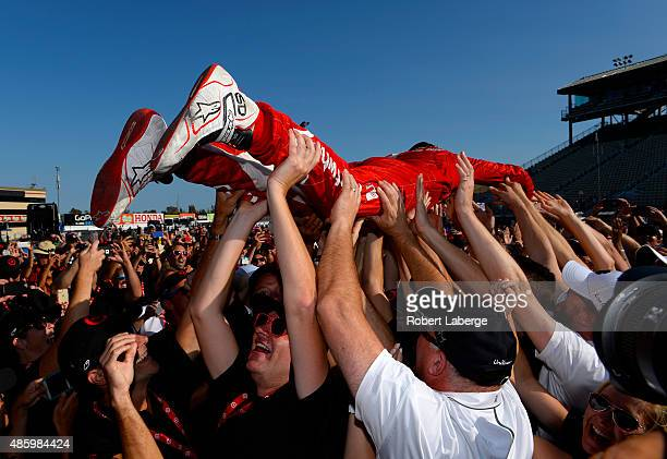 Scott Dixon of New Zealand driver of the Target Chip Ganassi Racing Chevrolet Dallara crowd surfs at the Championship Trophy presentation stage after...