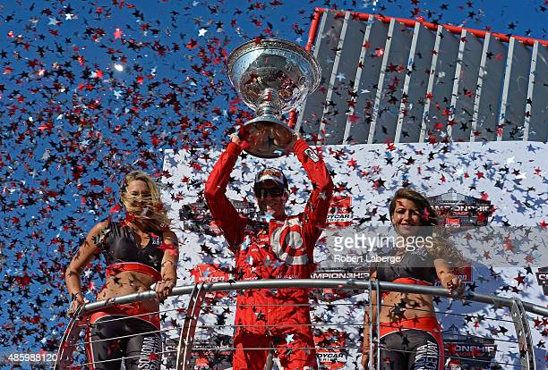 Scott Dixon of New Zealand driver of the Target Chip Ganassi Racing Chevrolet Dallara lifts the IndyCar Championship trophy after winning the Verizon...
