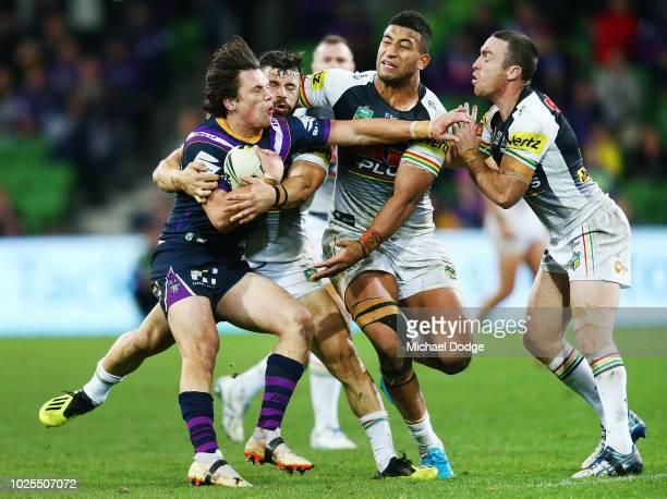 Scott Drinkwater of the Storm is tackled by Josh Mansour Viliame Kikau and James Maloney of the Panthers during the round 25 NRL match between the...