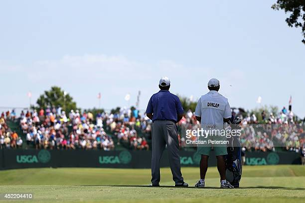 Scott Dunlap stands with his caddie on the 18th hole during the final round of the 2014 US Senior Open Championship at Oak Tree National on July 13...