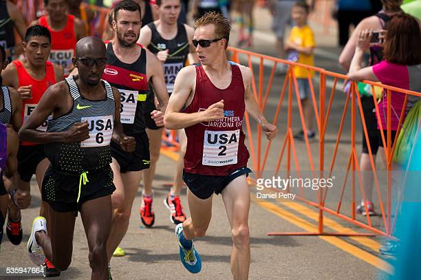 Scott Fauble of the United States looks over to Abdi Abdirahman of the United States during the men's elite competition during the Bolder Boulder 10K...