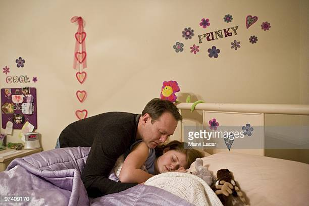Scott Forhetz prays over his daughter as the family winds down after an evening at the church where their entire family participated in a purity ring...