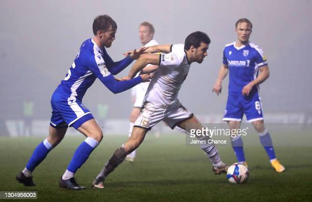 Scott Fraser of Milton Keynes Dons is challenged by Robbie Cundy of Gillingham FC during the Sky Bet League One match between Gillingham and Milton...