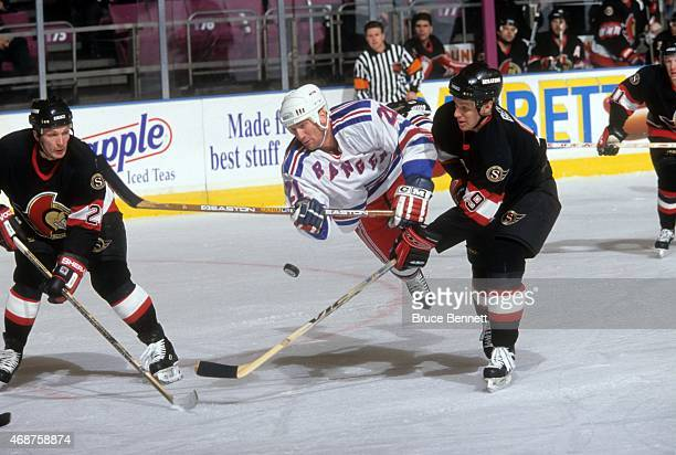 Scott Fraser of the New York Rangers goes for the puck as he's tripped up by Bill Berg of the Ottawa Senators circa 1999 at the Madison Square Garden...
