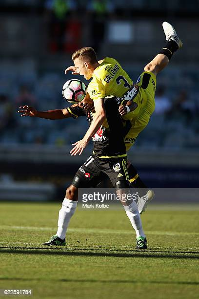 Scott Galloway of Mariners jumps over the top of Roy Krishna of the Phoenix to head the ball during the round six A-League match between the Central...