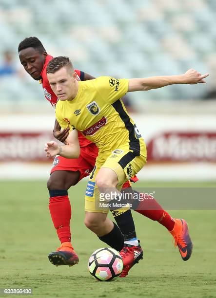 Scott Galloway of the Mariners is challenged by Mark Ochieng of United during the round 18 A-League match between the Central Coast Mariners and...