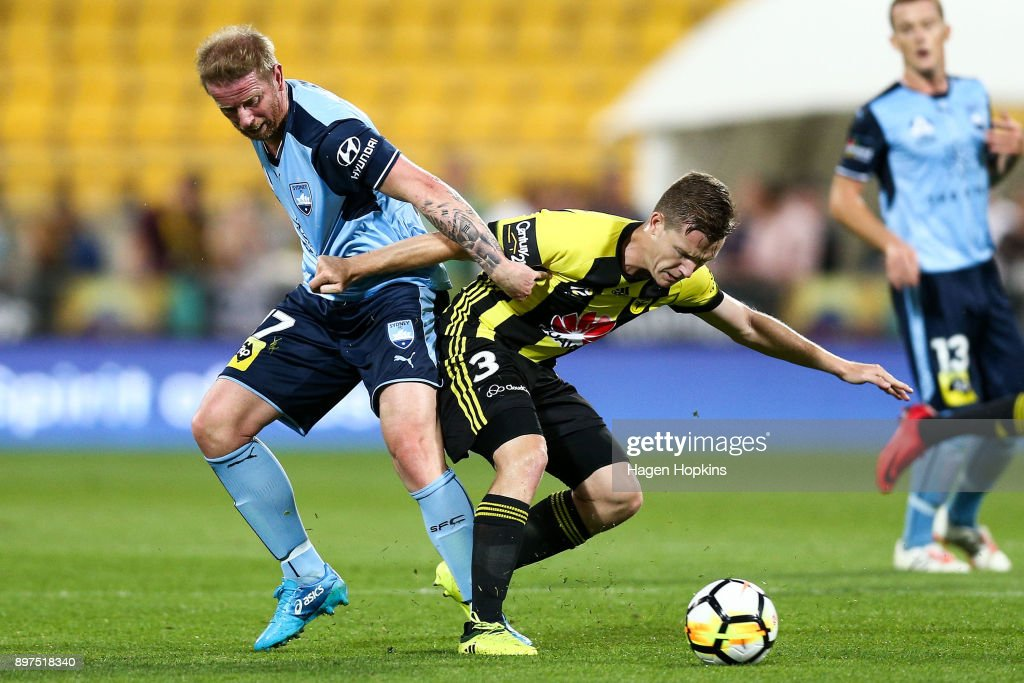 Scott Galloway of the Phoenix is challenged by Rhyan Grant of Sydney FC during the round 12 A-League match between the Wellington Phoenix and Sydney FC at Westpac Stadium on December 23, 2017 in Wellington, New Zealand.