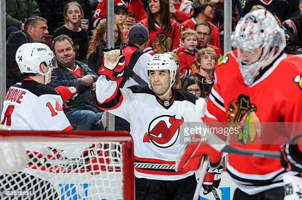 Scott Gomez and Adam Henrique of the New Jersey Devils celebrate behind goalie Corey Crawford of the Chicago Blackhawks after the Devils scored in...