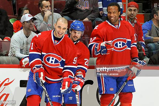 Scott Gomez Brian Gionta and Georges Laraque of the Montreal Canadiens laugh together during the warm up before the NHL game against the Buffalo...