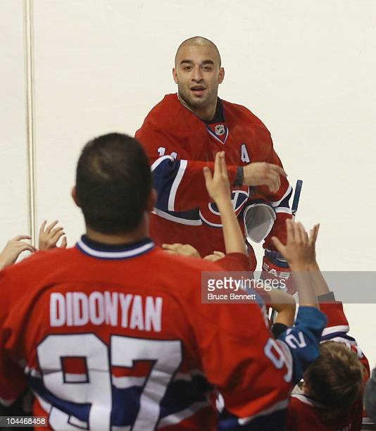 Scott Gomez of the Montreal Canadiens flips a puck to fans prior to the game against the Ottawa Senators at the Bell Centre on September 24 2010 in...