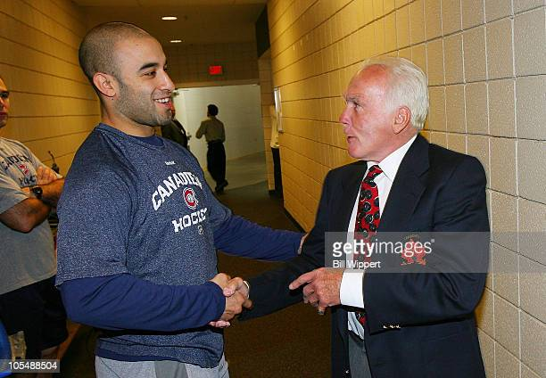 Scott Gomez of the Montreal Canadiens shakes hands with former Canadien Hall of Fame member Henri Richard prior to their game against the Buffalo...
