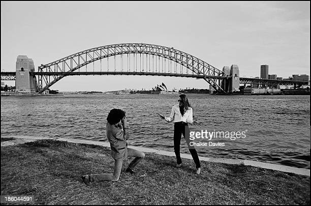 Scott Gorham and Phil Lynott from Thin Lizzy take photos of each other in front of the Sydney Harbour Bridge and Opera House during their Australian...