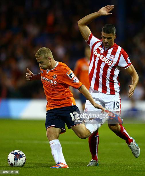 Scott Griffiths of Luton Town is closed down by Jonathan Walters of Stoke City during the Capital One Cup second round match between Luton Town and...
