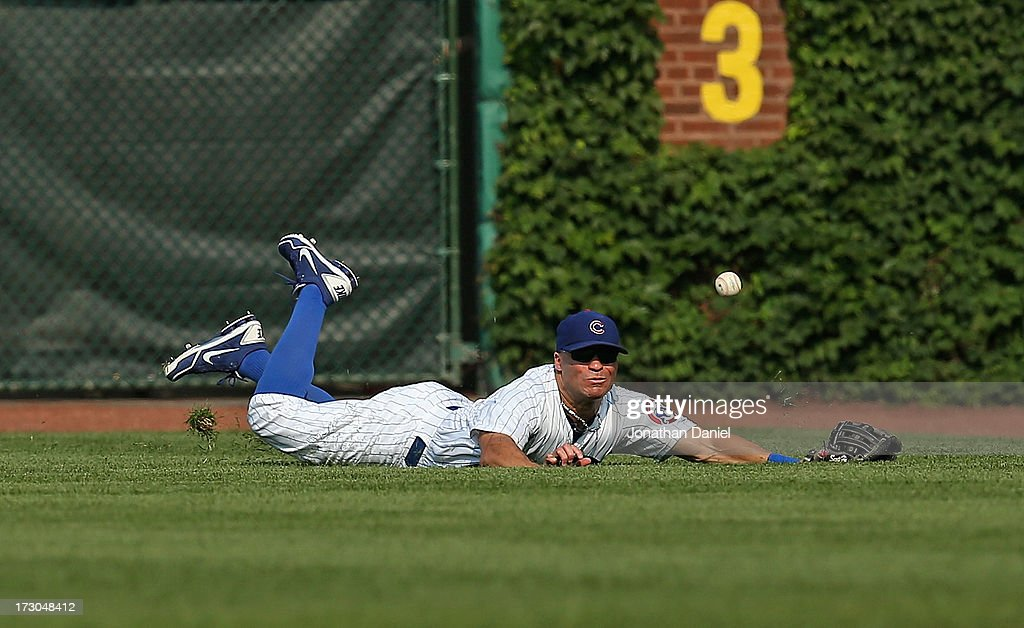 Scott Hairston #21 of the Chicago Cubs dives in vain for a ball hit by Jose Tabata of the Pittsburgh Pirates in the 7th inning at Wrigley Field on July 5, 2013 in Chicago, Illinois.